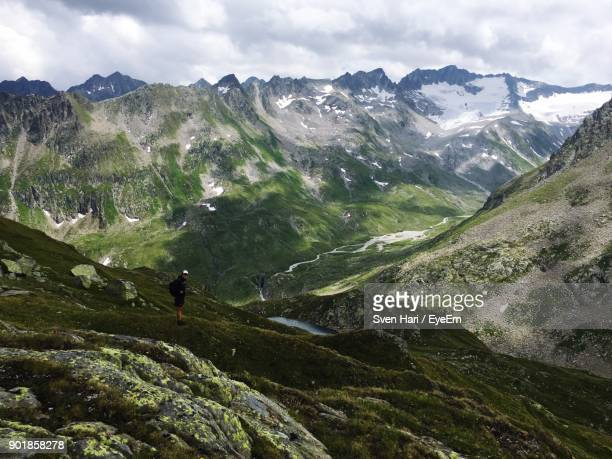 Side View Of Hiker Standing On Mountain Against Cloudy Sky