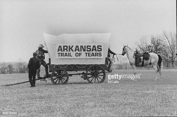Side view of horsedrawn covered wagon w trekkers nearby banner on it which reads Arkansas Trail of Tears which signifies reenaction of 1000mile...