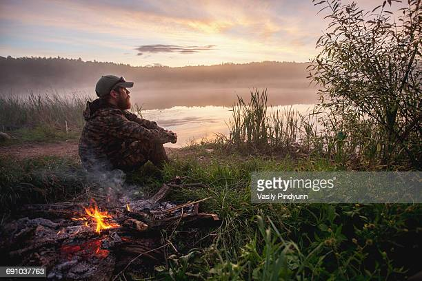 side view of hunter sitting by bonfire on field at lakeshore during sunset - hunting stock pictures, royalty-free photos & images