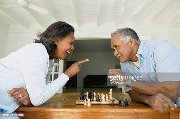 side view of husband and wife playing chess - playing chess stock pictures, royalty-free photos & images