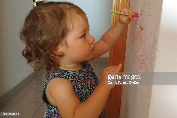 Side View Of Innocent Girl Drawing On Wall At Home