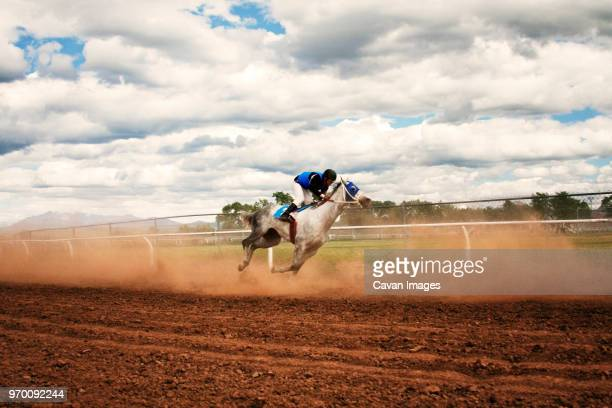 side view of jockey riding horse at competition - horse racing stock pictures, royalty-free photos & images