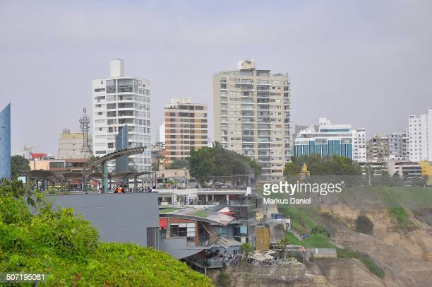 CONTENT] Side view of Larcomar open air shopping mall and apartment buildings at the Pacific Ocean coast in the Miraflores city district of Lima Peru...