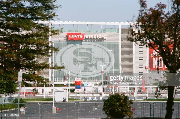 Side view of Levi's Stadium home of the San Francisco 49ers football team viewed through trees across a parking lot in the Silicon Valley Santa Clara...