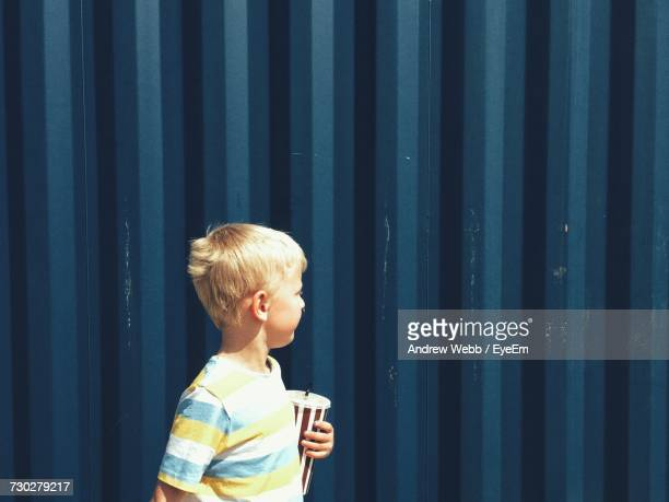 Side View Of Little Boy Standing Against Blue Wall On Sunny Day
