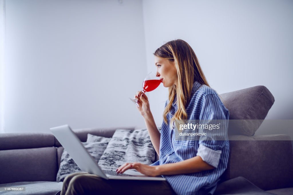 Side view of lovely caucasian brunette in stripped shirt sitting on couch in living room, drinking wine and using laptop. : Stock Photo