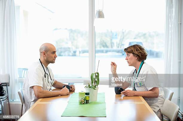 Side view of male and female doctors discussing while having coffee at desk in hospital