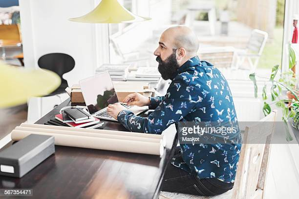 Side view of male architect sitting at table in home office