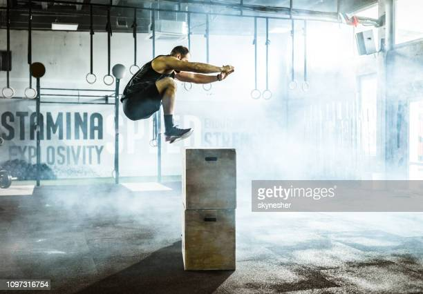 side view of male athlete jumping on crate during sport training in a gym. - crossfit stock pictures, royalty-free photos & images
