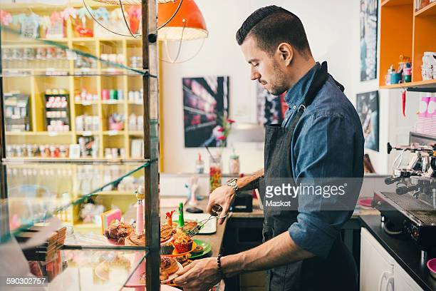 Side view of male barista using tongs to remove cupcake at cafe counter