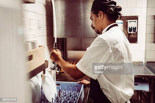 Side view of male chef spraying water on plates in commercial kitchen