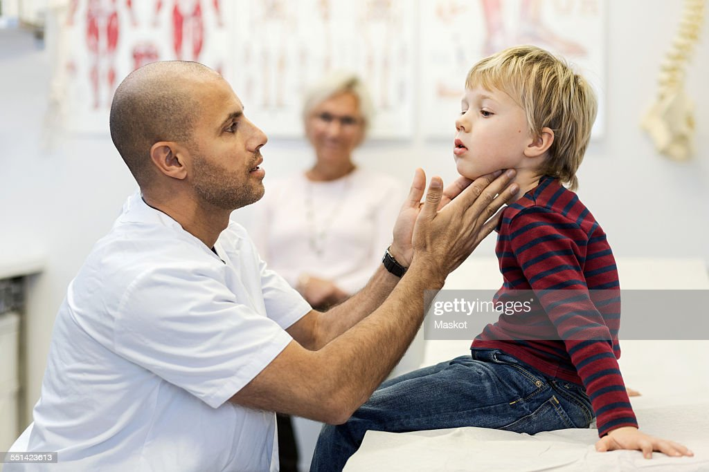 Side view of male doctor checking boys throat at clinic : Stock Photo