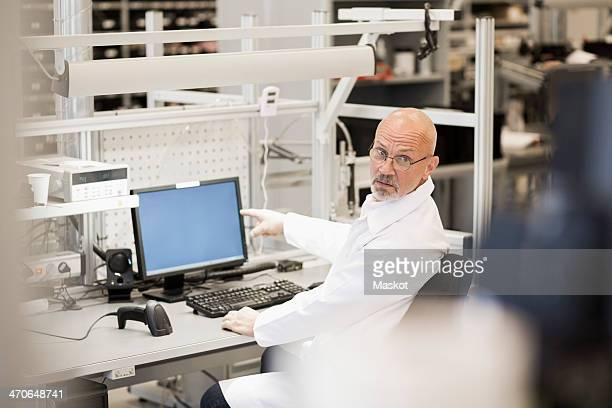 Side view of male engineer pointing at computer in manufacturing industry