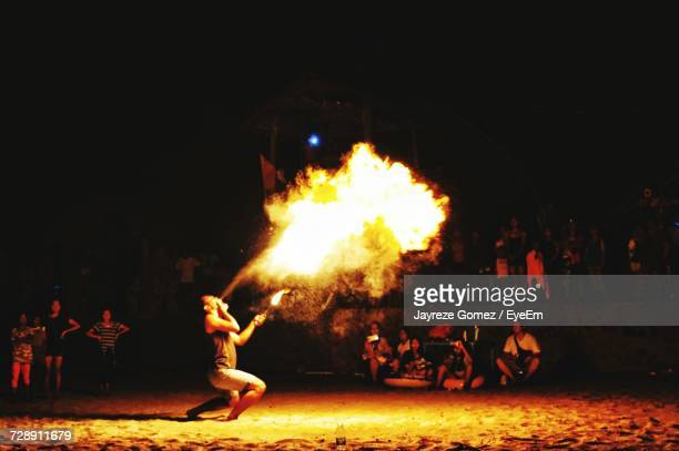 Side View Of Male Fire-Eater Performing At Beach During Night