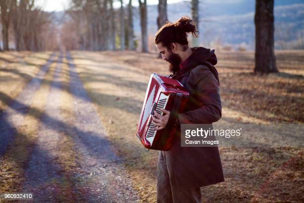 side view of male hipster playing accordion at field during vacation - accordion instrument stock pictures, royalty-free photos & images