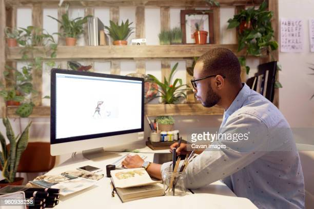 side view of male illustrator making painting on computer in creative office - illustrator stock photos and pictures