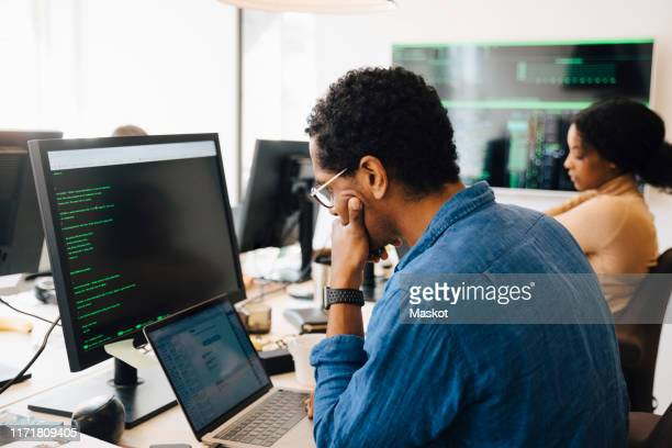 side view of male it professional using laptop while sitting by female coworker in office - programmer stock pictures, royalty-free photos & images