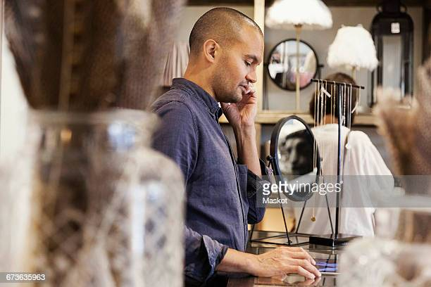 Side view of male owner talking on phone while standing at store
