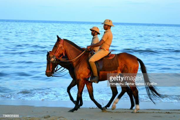 Side View Of Male Police Officers Riding Horses At Beach
