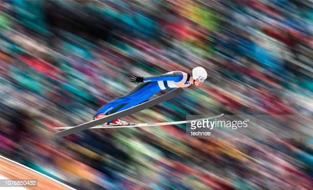 side view of male ski jumper in mid-air against blurred background - ski jumping stock pictures, royalty-free photos & images