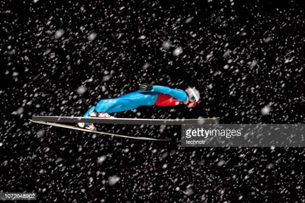 seitenansicht des männlichen skispringer in der luft während schneesturm - kurzzeitfotografie stock-fotos und bilder