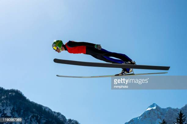 side view of male ski jumper in mid-air - ski jumping stock pictures, royalty-free photos & images