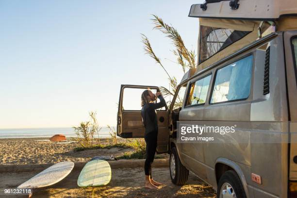 side view of male surfer having drink outside mini van on san onofre state beach - mini van stock pictures, royalty-free photos & images