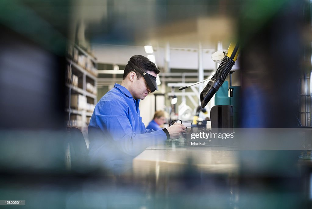 Side view of male technician wearing protective eyewear working in industry : Stock-Foto
