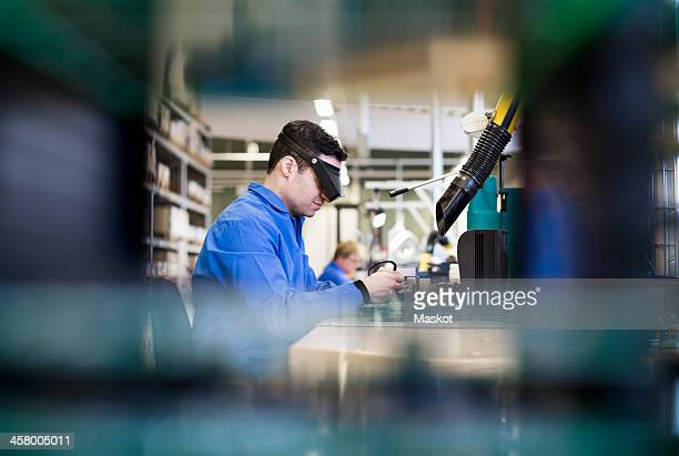 Side view of male technician wearing protective eyewear working in industry