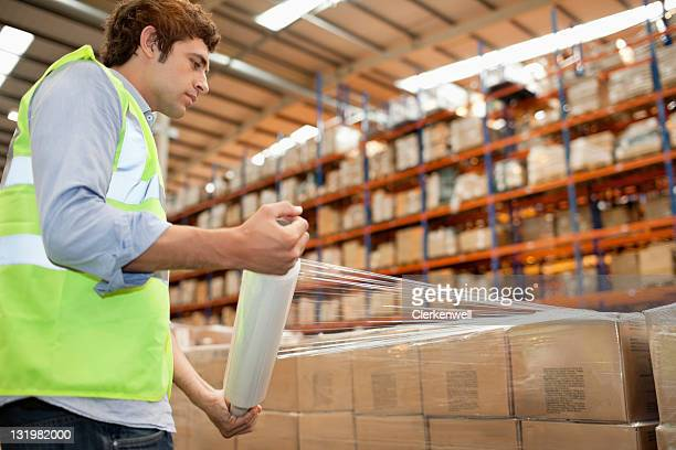 Side view of male warehouse worker wrapping cardboard cardboard boxes