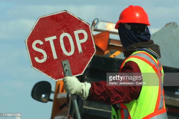 side view of male worker holding stop sign against vehicle on road - stop sign stock pictures, royalty-free photos & images