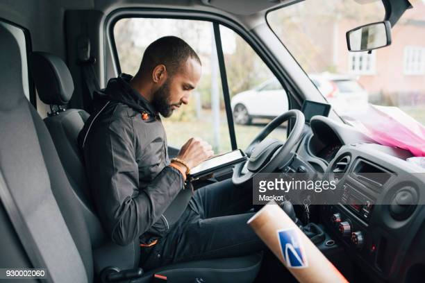 side view of male worker using digital tablet while sitting in delivery van - vervoermiddel stockfoto's en -beelden