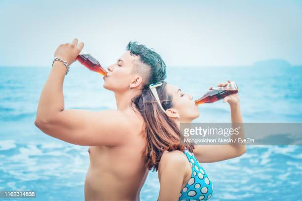 side view of man and woman drinking cola in sea against sky - coca cola imagens e fotografias de stock
