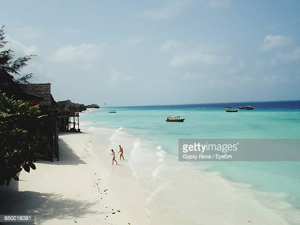 side view of man and woman walking at beach - zanzibar island stock photos and pictures