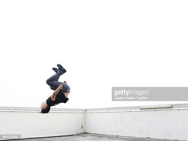 Side View Of Man Backflipping On Building Terrace Against Sky