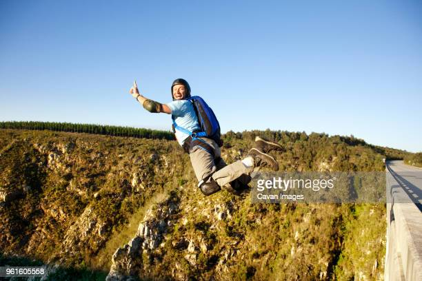 side view of man base jumping against clear sky - padding stock photos and pictures