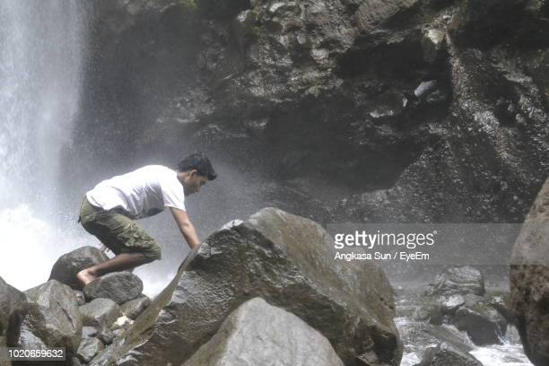 Side View Of Man Bending On Rock Against Waterfall