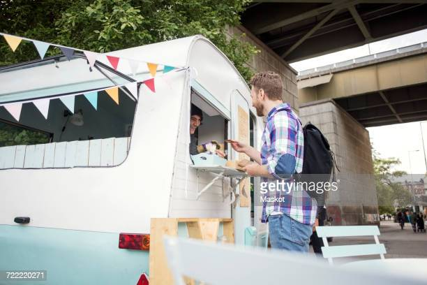 Side view of man buying food from owner in food truck