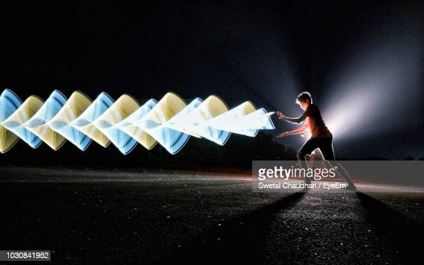 side view of man by light painting on road at night - lichtmalerei stock-fotos und bilder