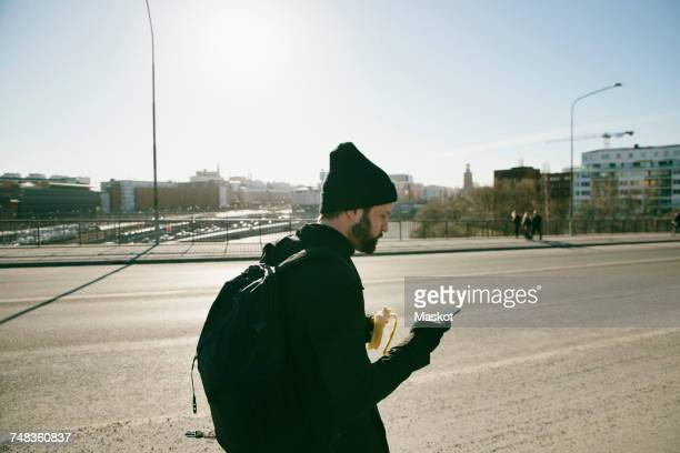 Side view of man carrying backpack having banana while using mobile phone on city street against clear sky