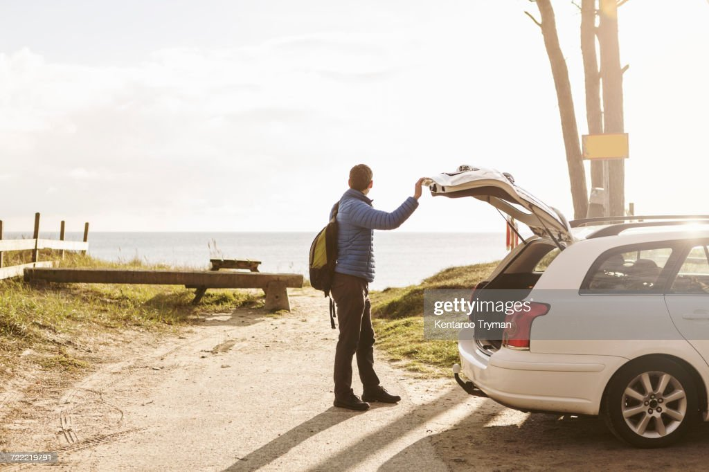 Side view of man carrying backpack while standing by car on footpath : Stock Photo