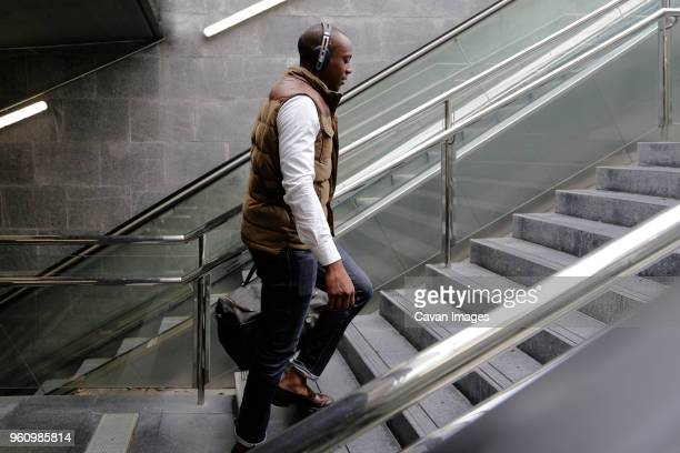 side view of man climbing steps at subway station - staircase stock pictures, royalty-free photos & images
