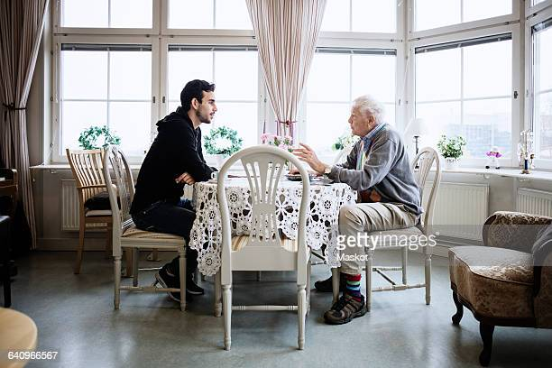 Side view of man communicating with caretaker at dining table