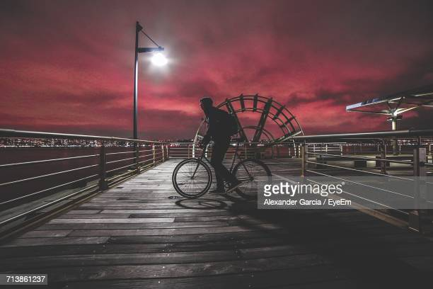 Side View Of Man Cycling On Footbridge Against Sky At Night