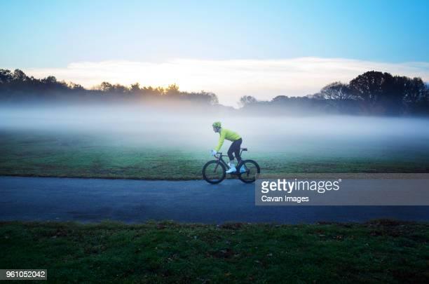 side view of man cycling on street amidst grassy field in foggy weather - radsport wettbewerb stock-fotos und bilder
