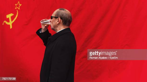side view of man drinking beer against former ussr flag - bandiera comunista foto e immagini stock