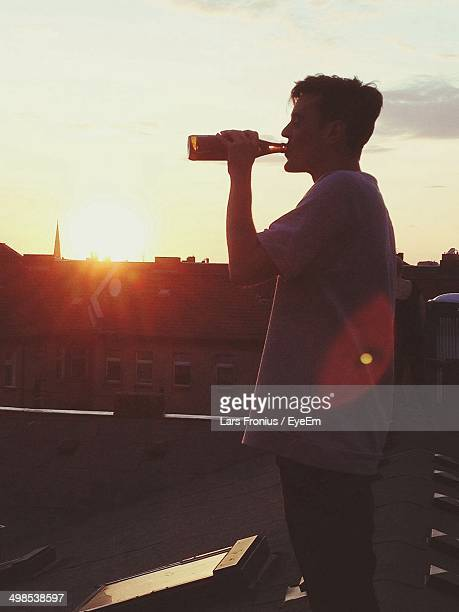 Side view of man drinking beer on rooftop at sunset