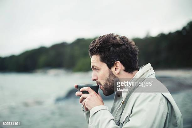 Side view of man drinking coffee at sea shore
