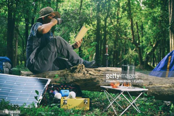 side view of man drinking coffee while reading book on fallen tree in forest - アウトドア ストックフォトと画像