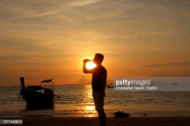 side view of man drinking drink from bottle at beach against sky during sunset - railay strand stock-fotos und bilder